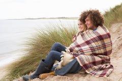 Pares adolescentes que se sientan en dunas de arena Foto de archivo libre de regalías