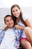 Pares adolescentes que se sientan en las escaleras Fotos de archivo libres de regalías