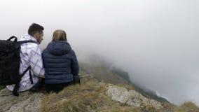 Pares adolescentes que se sientan encima de la montaña rocosa que disfruta de la visión y de besarse - almacen de video