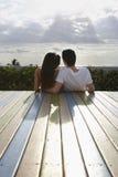 Pares adolescentes que sentam-se na plataforma que olha a vista Imagens de Stock Royalty Free