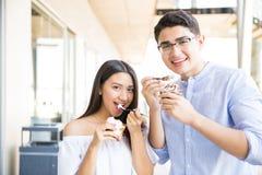 Pares adolescentes que têm o gelado na data no shopping imagem de stock royalty free