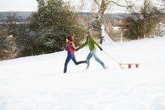 Pares adolescentes que tiran del trineo a través del campo Nevado Foto de archivo