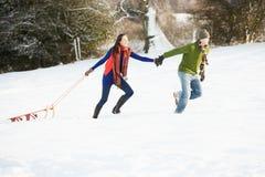 Pares adolescentes que tiran del trineo a través del campo Nevado Fotografía de archivo