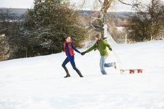 Pares adolescentes que tiran del trineo a través del campo Nevado Imagen de archivo libre de regalías