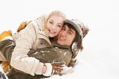 Pares adolescentes románticos que se divierten en nieve Imagenes de archivo