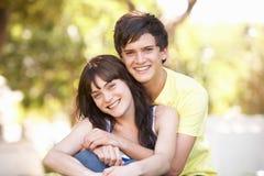 Pares adolescentes románticos que se sientan en parque Imagen de archivo