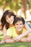 Pares adolescentes románticos que se sientan en parque Foto de archivo