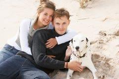 Pares adolescentes românticos na praia com cão Imagens de Stock Royalty Free