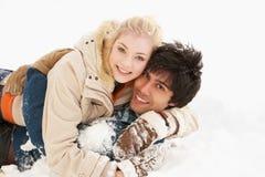 Pares adolescentes românticos que têm o divertimento na neve Foto de Stock