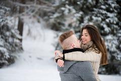 Pares adolescentes romancing en bosque del invierno Imágenes de archivo libres de regalías