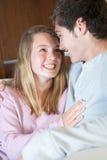 Pares adolescentes románticos que se sientan en el sofá en el país Imagen de archivo libre de regalías