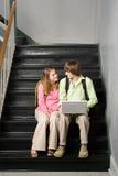 Pares adolescentes sentados en la escalera de la escuela Imagen de archivo libre de regalías