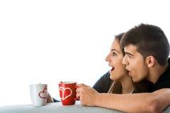 Pares adolescentes sorprendidos que miran a un lado. Fotografía de archivo