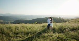 Pares adorables jovenes que abrazan, besándose en la región densa verde de la montaña Verano, puesta del sol Metas de los pares almacen de metraje de vídeo