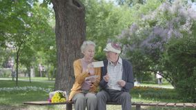 Pares adultos adorables del retrato que miran las fotos viejas que recuerdan momentos felices sentarse en un banco en el parque m almacen de metraje de vídeo