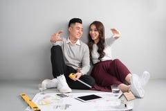 Pares adultos asiáticos jovenes que se sientan en Flor que planea el nuevo desig casero Foto de archivo