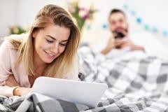 Pares adultos con el ordenador portátil en cama imagenes de archivo
