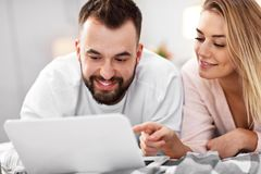 Pares adultos con el ordenador portátil en cama imágenes de archivo libres de regalías