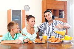 Pares adultos con un adolescente durante el desayuno Imagen de archivo libre de regalías