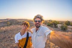 Pares adultos de sorriso que tomam o selfie no deserto de Namib, parque nacional de Namib Naukluft, destino principal do curso em fotografia de stock royalty free
