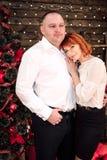 Pares adultos felices que abrazan cerca del árbol de navidad Tiro retocado Imagenes de archivo