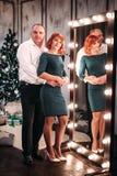 Pares adultos felices que abrazan cerca del árbol de navidad Tiro retocado Fotos de archivo libres de regalías