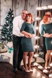 Pares adultos felices que abrazan cerca del árbol de navidad Tiro retocado Imágenes de archivo libres de regalías