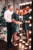 Pares adultos felices que abrazan cerca del árbol de navidad Tiro retocado Imagen de archivo