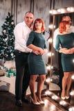 Pares adultos felices que abrazan cerca del árbol de navidad Tiro retocado Imagen de archivo libre de regalías