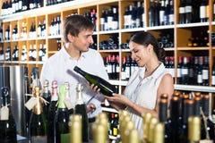 Pares adultos felices que eligen junto el vino Imagenes de archivo