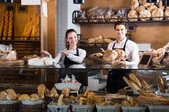 Pares adultos felices que venden los pasteles y los panes Imagen de archivo libre de regalías