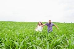 Pares adultos jovenes cariñosos felices que pasan tiempo en el campo el día soleado Imágenes de archivo libres de regalías