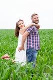 Pares adultos jovenes cariñosos felices que pasan tiempo en el campo el día soleado Fotografía de archivo libre de regalías