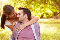 Pares adultos jovenes felices que se relajan en el campo Imagenes de archivo