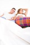 Pares adultos jovenes que duermen en la cama en dormitorio Imagenes de archivo
