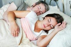 Pares adultos jovenes que duermen en la cama en dormitorio Fotografía de archivo libre de regalías