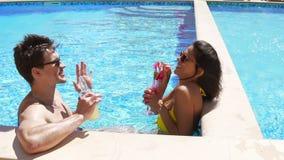 Pares adultos jovenes que ligan y que hablan en la piscina Fiesta en la piscina del verano Tiro a cámara lenta almacen de video