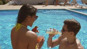 Pares adultos jovenes que ligan y que hablan en la piscina y los cócteles de consumición, haciendo alegrías Piscina del verano metrajes