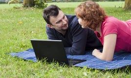 Pares adultos jovenes que se relajan en el parque Foto de archivo libre de regalías
