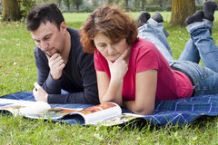 Pares adultos jovenes que se relajan en el parque Imágenes de archivo libres de regalías