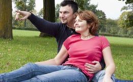 Pares adultos jovenes que se relajan en el parque Imagenes de archivo