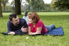 Pares adultos jovenes que se relajan en el parque Imagen de archivo libre de regalías