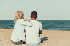 Pares adultos jovenes que se sientan en la playa y que miran horizonte de mar Foto de archivo