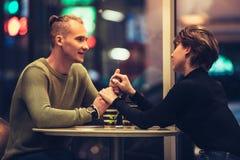 Pares adultos jovenes que tienen una fecha en café y que beben el café que lleva a cabo las manos Fotos de archivo