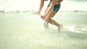 Pares adultos maried felices que se divierten y que juegan en el mar
