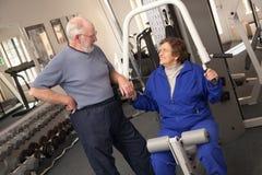 Pares adultos mayores activos que se resuelven junto en el gimnasio Imagen de archivo