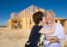 Pares adultos mayores chinos que se besan en Front Of New House Frame Fotografía de archivo