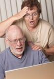 Pares adultos mayores chocados que se divierten en el ordenador Foto de archivo libre de regalías