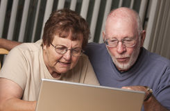 Pares adultos mayores confusos que se divierten en el ordenador Fotografía de archivo