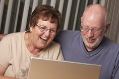 Pares adultos mayores de risa que se divierten en el ordenador Fotografía de archivo